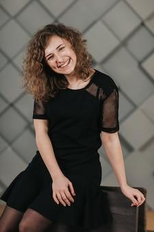 Meisje met krullen in een zwarte jurk, zittend op een stoel