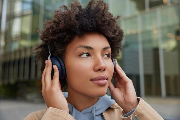 Meisje met krullend afro-haar geniet van nieuw audionummer in draadloze hoofdtelefoons luistert audio-opnames houdt van audio-webinhoud nonchalant gekleed poseert