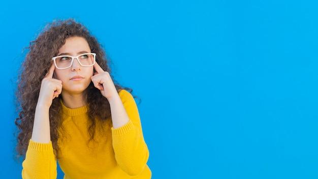 Meisje met krullend haar dat de ruimte van het exemplaar van glazen draagt