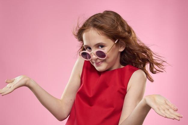 Meisje met krullend haar donkere ronde bril leuke rode jurk roze