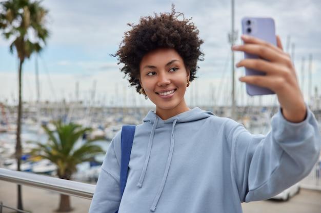 Meisje met krullend haar gekleed in casual hoodie maakt selfie portret op smartphone wandelingen in de haven geniet van een goede dag