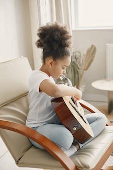 Meisje met krullend haar. gitaar leren spelen. klein meisje in een stoel.