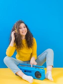Meisje met krullend haar glimlacht en luistert naar muziek