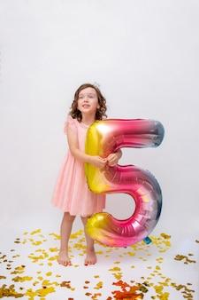Meisje met krullend haar in een feestelijke jurk staat met een opblaasbare bal met het nummer vijf op een witte achtergrond met gouden confetti. verjaardag