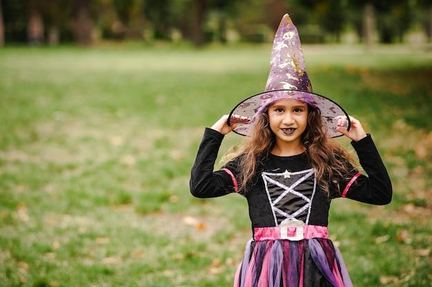 Meisje met krullend haar in een heksenkostuum voor halloween