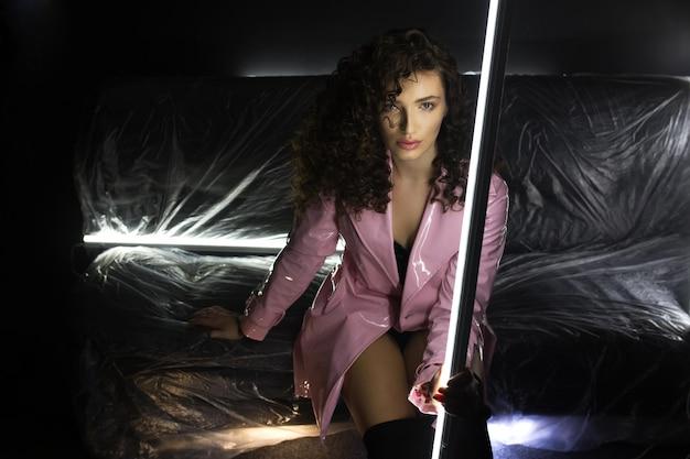 Meisje met krullend haar in gelakte roze jas