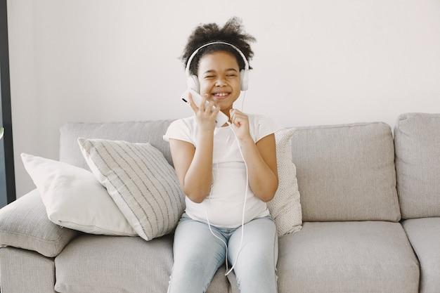 Meisje met krullend haar. kind droogt muziek in koptelefoon. veel plezier thuis.