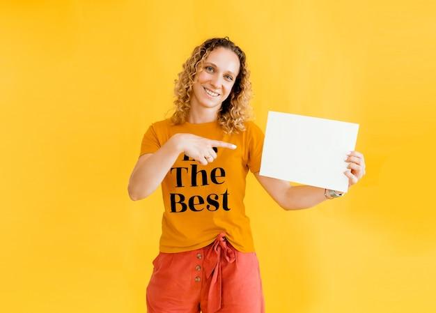 Meisje met krullend haar met een lege kaart. geïsoleerd op gele achtergrond lachende vrouw portret.