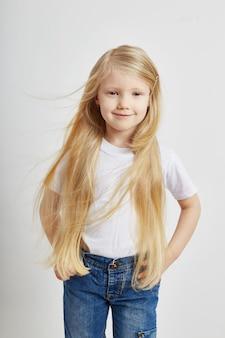 Meisje met lang blond haar en in spijkerbroek poseren op een witte muur. joy fun, jonge model kindermode. school voor modellen van kinderen.