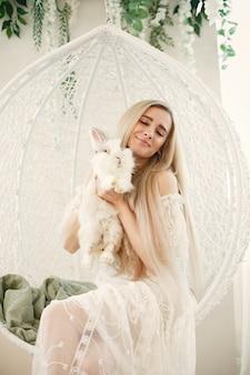 Meisje met lang blond haar met een wit konijn in haar armen.