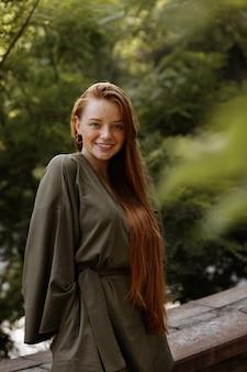 Meisje met lang gezond rood haar op een groene zomer ruimte
