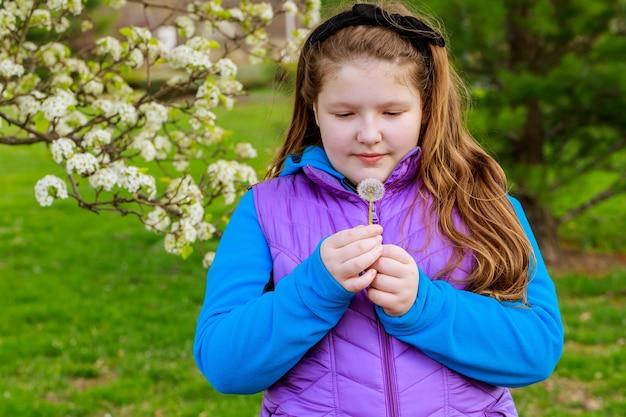 Meisje met lang haar en bandana kijkt naar een paardebloem in het voorjaar
