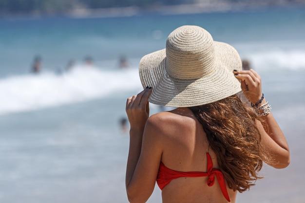 Meisje met lang haar en met een hoed zittend op een strand