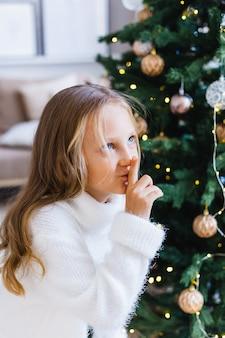 Meisje met lang haar in de buurt van de kerstboom