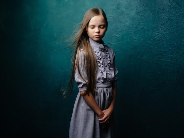 Meisje met lang haar in een jurk die een droevige blik op een groene achtergrond stelt