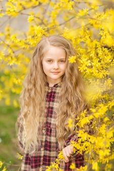 Meisje met lang haar in gele bloemen. een kind op de achtergrond van forsythia. lente portret van een kind