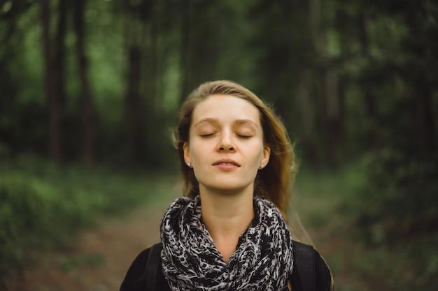 Meisje met lang haar loopt door het bos.