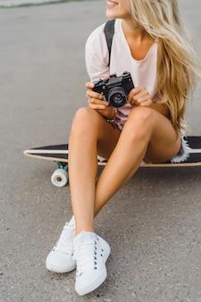 Meisje met lang haar met skateboard fotograferen op camera. straat, actieve sporten