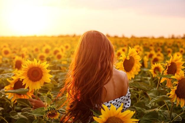 Meisje met lang haar staat met haar rug in het veld met bloeiende zonnebloemen in de stralen van de omgeving...