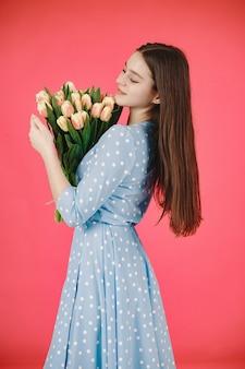Meisje met lang haar. vrouw met een boeket bloemen. dame in een blauwe jurk.