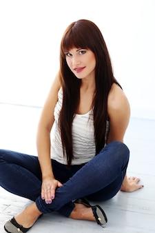 Meisje met lang haar zittend op de vloer
