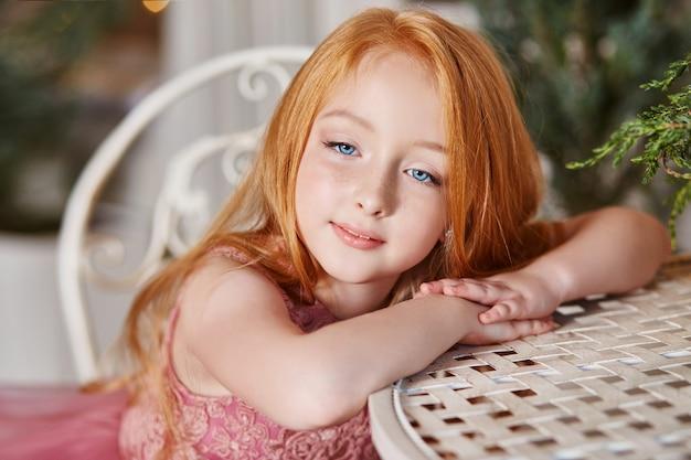 Meisje met lang rood haar roze jurk zittafel