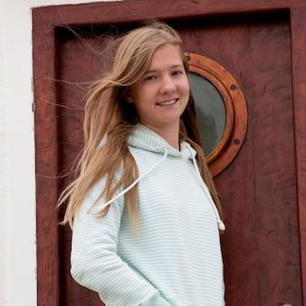 Meisje met lang winderig haar vóór deur met patrijspoort