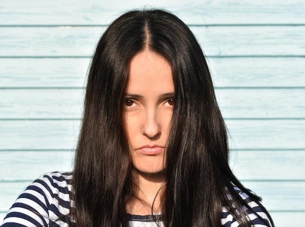 Meisje met lang zwart haar op houten achtergrond