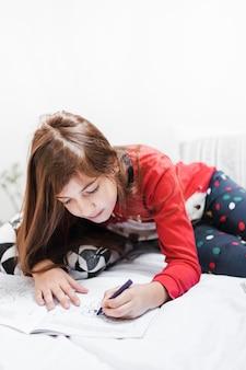 Meisje met lange haartekening met kleurpotlood op bed