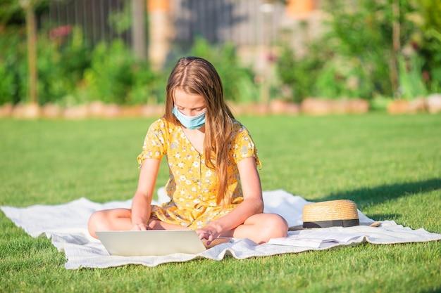 Meisje met laptop om buiten in het park te studeren