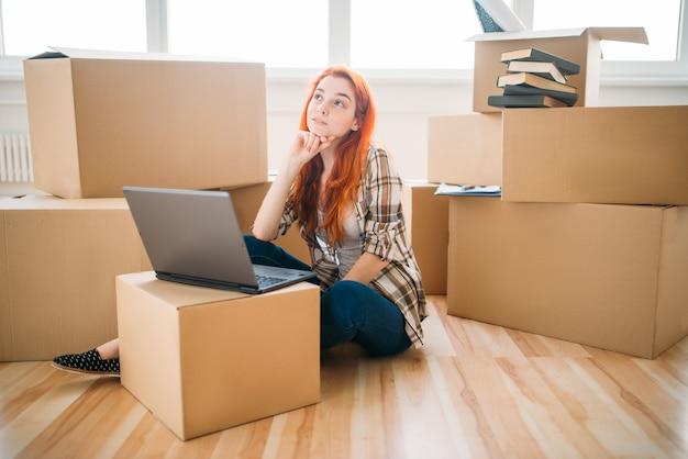 Meisje met laptop onder kartonnen dozen, nieuw huis