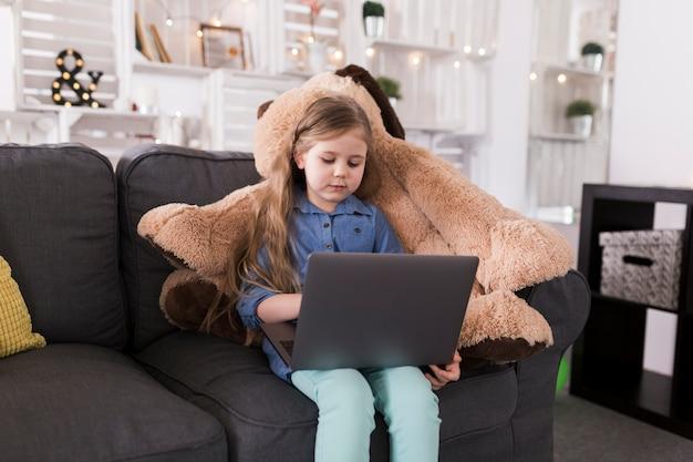 Meisje met laptop op de bank