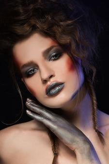 Meisje met lichte make-up. glamourportret van mooi vrouwenmodel met rood zilveren make-up en romantisch kapsel. glanzende briljante mode-markeerstift op de huid, sexy glanzende lippen en donkere wenkbrauwen