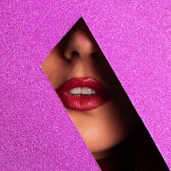 Meisje met lichte make-up, rode lippenstift kijkt door gat in violet papier