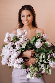 Meisje met lila bloemen in haar handen