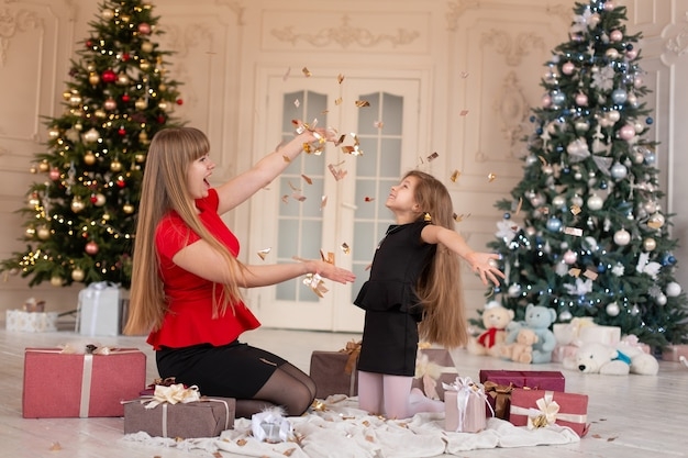 Meisje met maa gooit confetti en opent cadeautjes. kerstmagie. vrolijke momenten van een gelukkige jeugd.