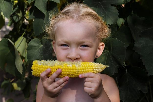Meisje met maïs onder natuurlijk licht. meisje met groenten. echte mensen.