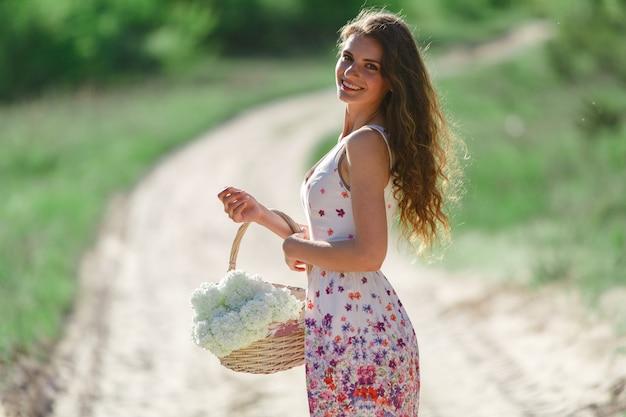 Meisje met mand met bloemen buitenshuis