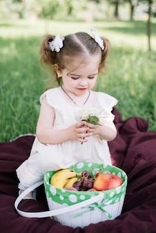 Meisje met mand van bloemen en vruchten die en van zonnige de zomerdag zitten genieten