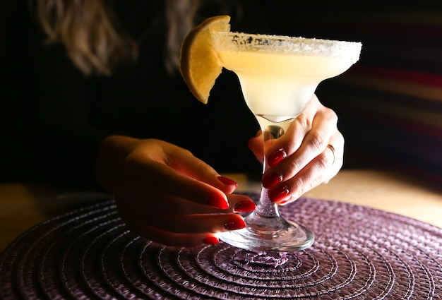 Meisje met margarita cocktail op tafel in het restaurant. alcoholische dranken. mooie handen.