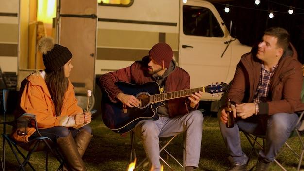 Meisje met marshmallow en een van zijn haar vrienden zingt op een gitaar rond het kampvuur in de koude nacht van de herfst. kamperen in de bergen.
