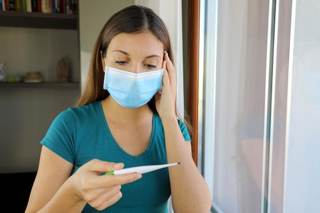 Meisje met masker op gezicht check koorts een symptoom van de ziekte van coronavirus 2019.