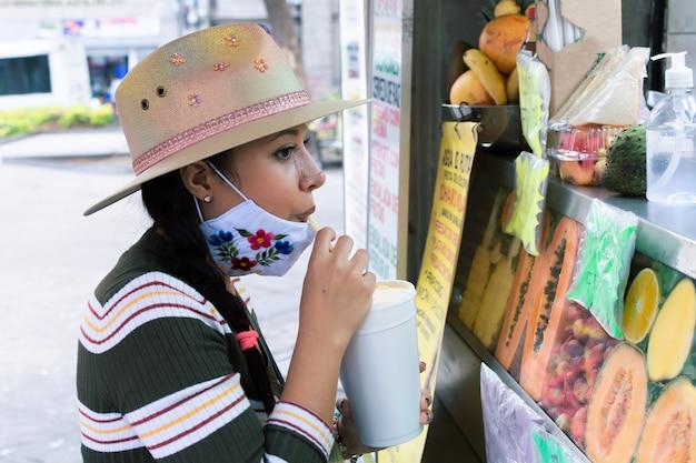 Meisje met maskergezicht dat vruchtensap drinkt