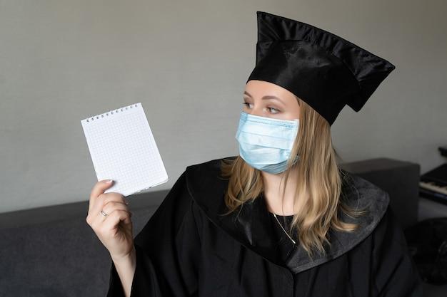 Meisje met medisch masker met afstudeerjurk hoed met een klein notitieboekje op grijze achtergrond