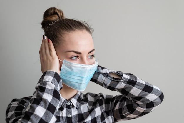 Meisje met medisch masker om haar te beschermen tegen virussen. coronavirus pandemie. vrouw met masker staan. mensen die in het ziekenhuis worden opgenomen, gediagnosticeerd, worden vaak in carantine (isolatie) geplaatst om te voorkomen dat ze corona verspreiden.
