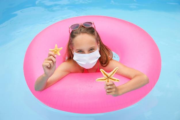 Meisje met medische masker op haar gezicht in zwembad.