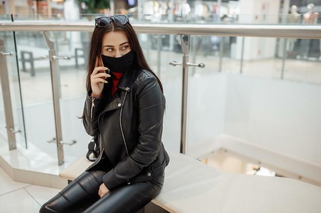 Meisje met medische zwarte masker en mobiele telefoon in een winkelcentrum. coronapandemie. een vrouw met een masker staat in een winkelcentrum. een meisje in een beschermend masker is winkelen in het winkelcentrum