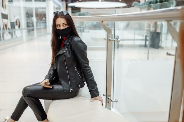 Meisje met medische zwarte masker en mobiele telefoon in een winkelcentrum. coronapandemie. vrouw met een masker staat in een winkelcentrum.