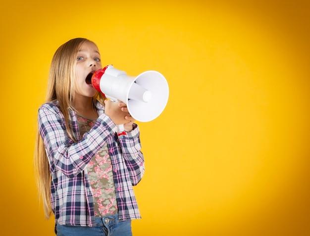 Meisje met megafoon schreeuwen, gele muur