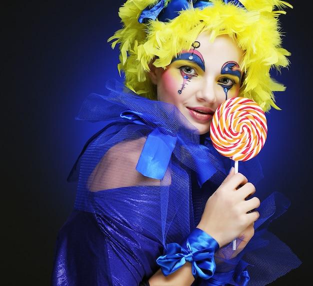Meisje met met creatieve make-up houdt lolly